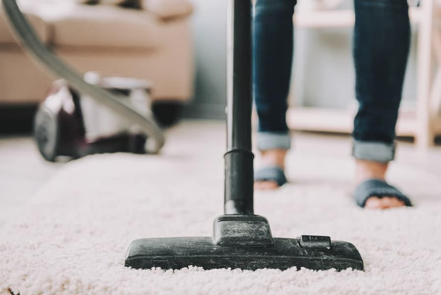 closeup woman in jeans cleaning carpet with vacuum machine