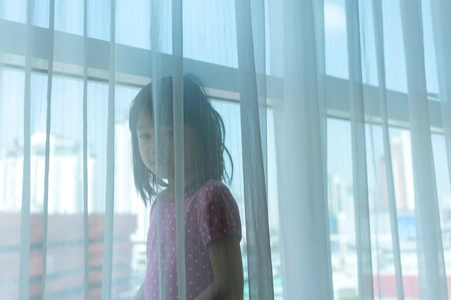 child girl playing behind curtain